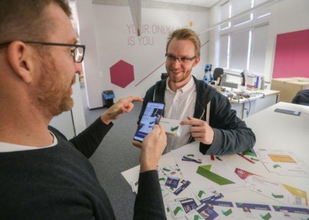 Authentic-Network-Gründer Frank Theeg (links) und Mitarbeiter Christian Günther demonstrieren, wie der grüne Haken auf einer Medikamenten-Verpackung mit dem Smartphone gescannt wird, um deren Echtheit zu überprüfen. Foto: Toni Söll